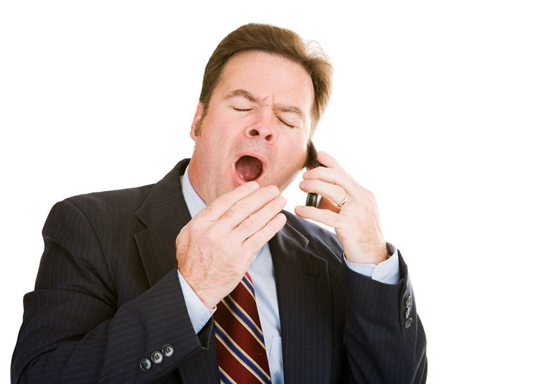 Man Yawning at Work While on the Phone