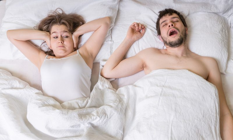 Woman Covering her Ears While Husband Snores
