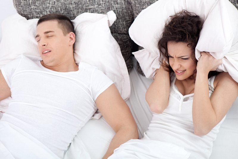 Woman Covers Her Ears with a Pillow Whild Husband Snores